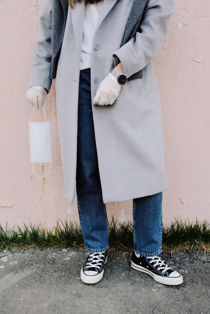 Woman in grey coat and converse sneakers wearing medical gloves and holding a face mask to protect herself from COVID-19.