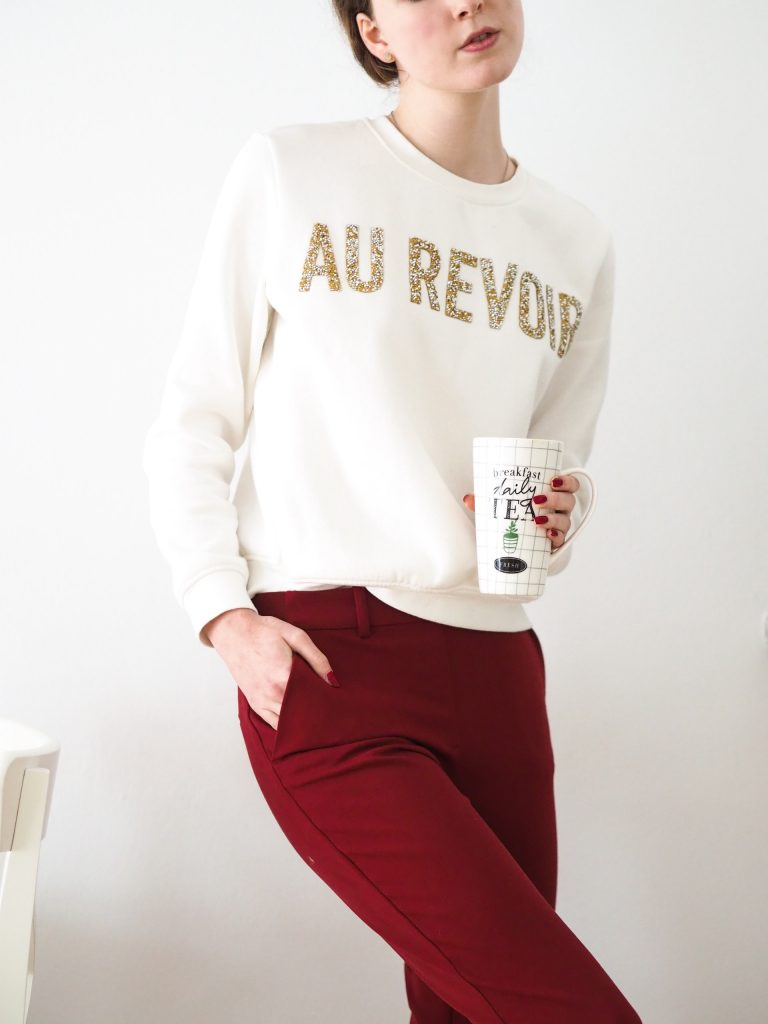 Woman wearing an Au Revoir sweatshirt and red trousers.