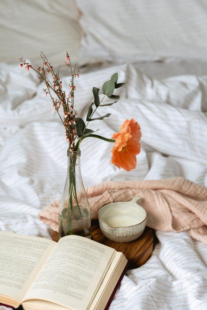 Bouquet of flowers in vase and book on an unmade bed.