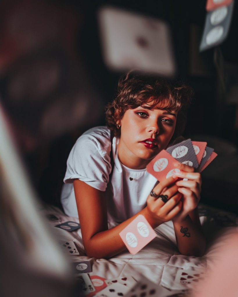 Woman holding playing cards while laying in bed.