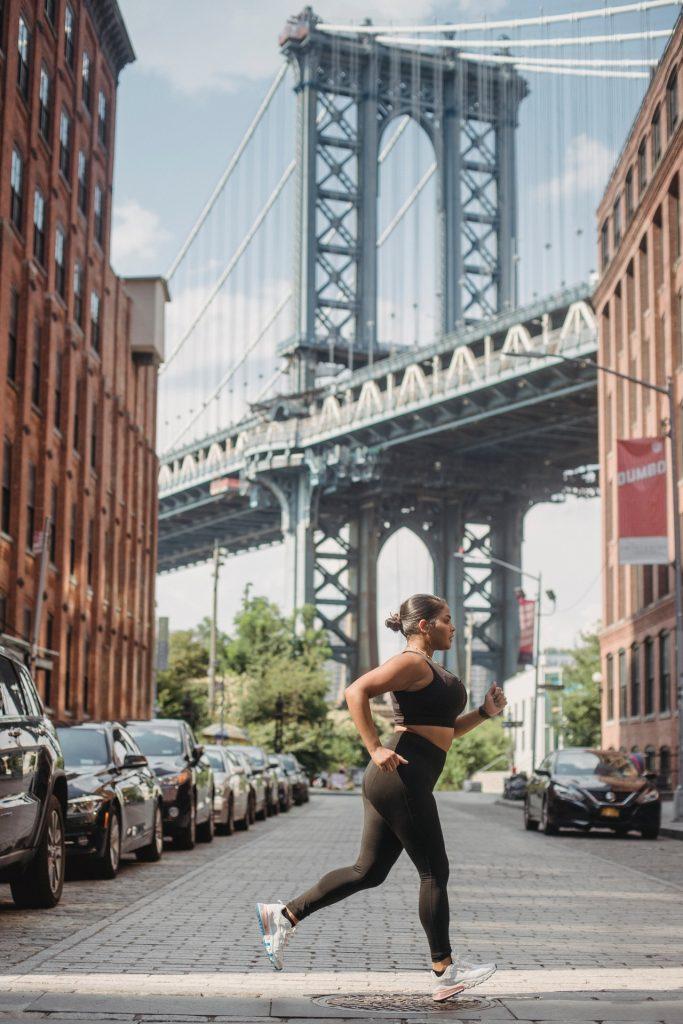 Woman in black leggings and black sports bra running under the Manhattan Bridge in Dumbo, Brooklyn.