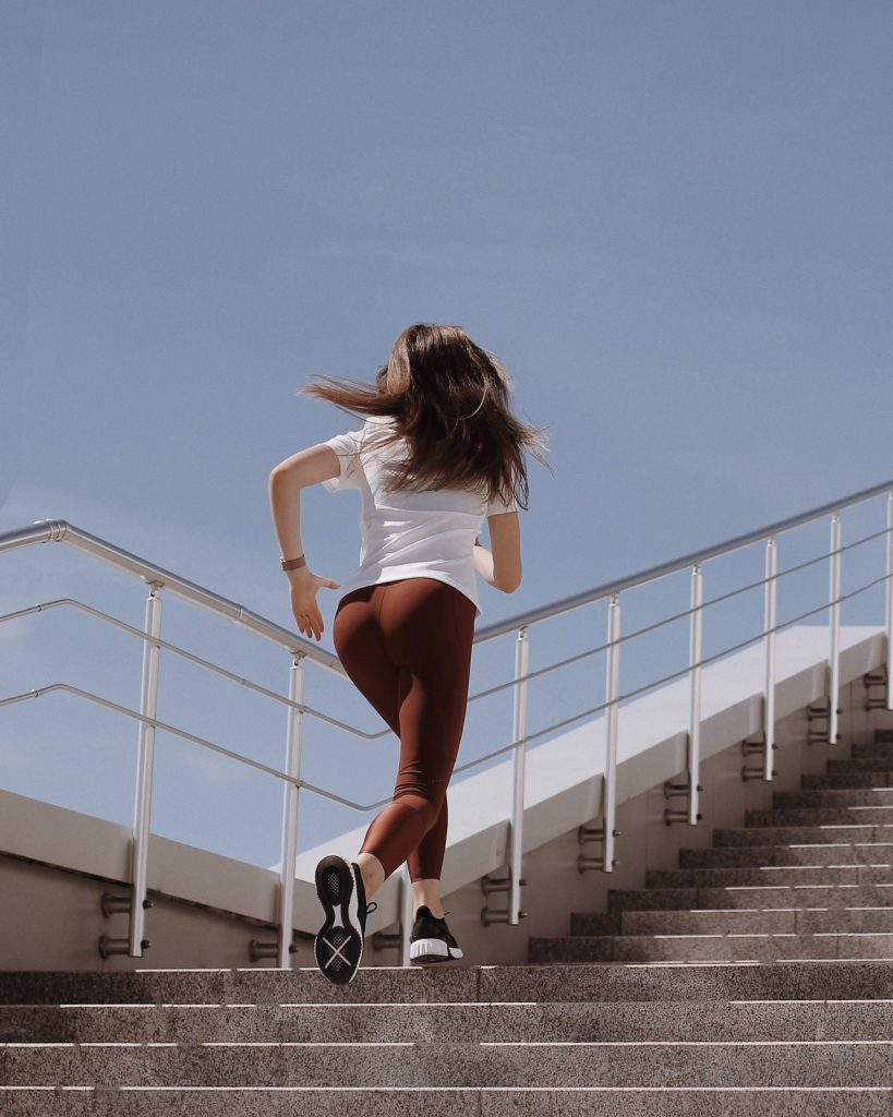 Woman in brown leggings and white shirt running up cement steps.
