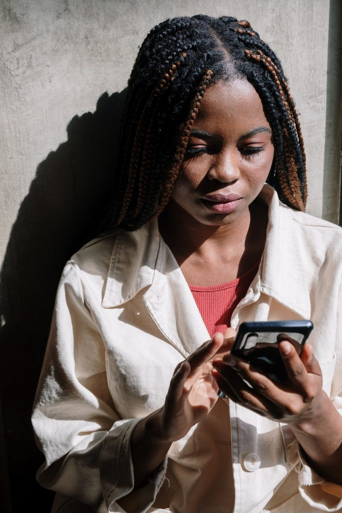 woman with braids using her iPhone outside.
