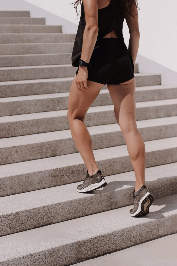 Woman with strong legs wearing workout clothing and going up cement steps.