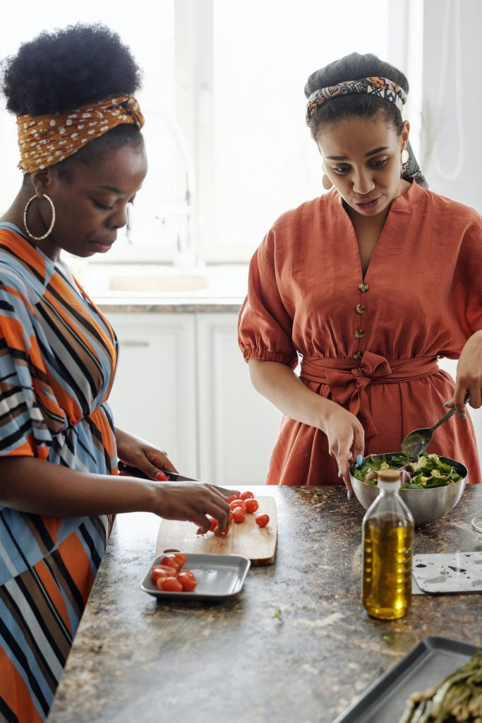Women helping each other prepare a salad on a kitchen island.