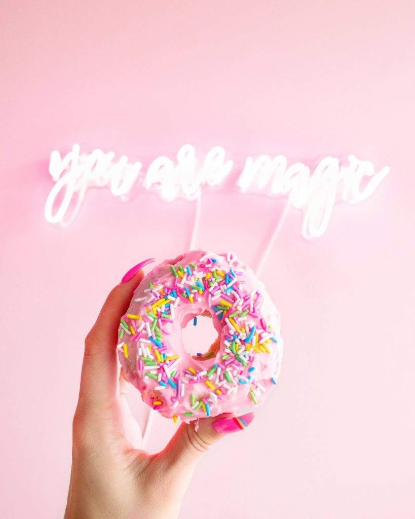 Hand with long pink nails holding a pink sprinkle donut in front of a light pink background. Photo by Karley Saagi.