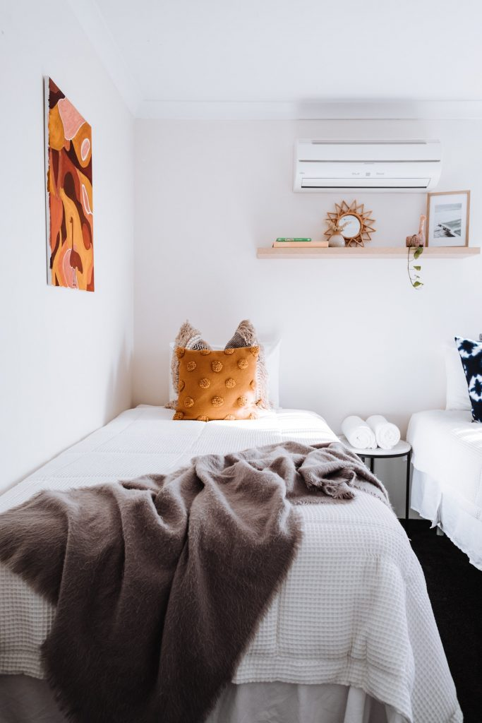Stylish bedroom with air conditioning unit on wall.