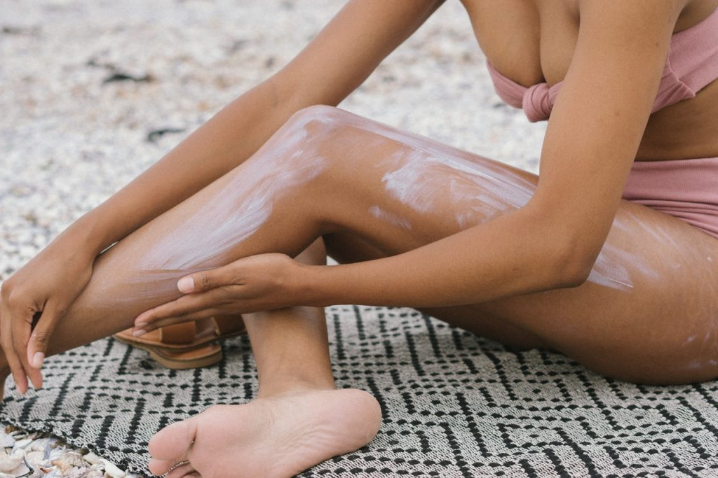 Woman in bathing suit applying sunscreen to legs.