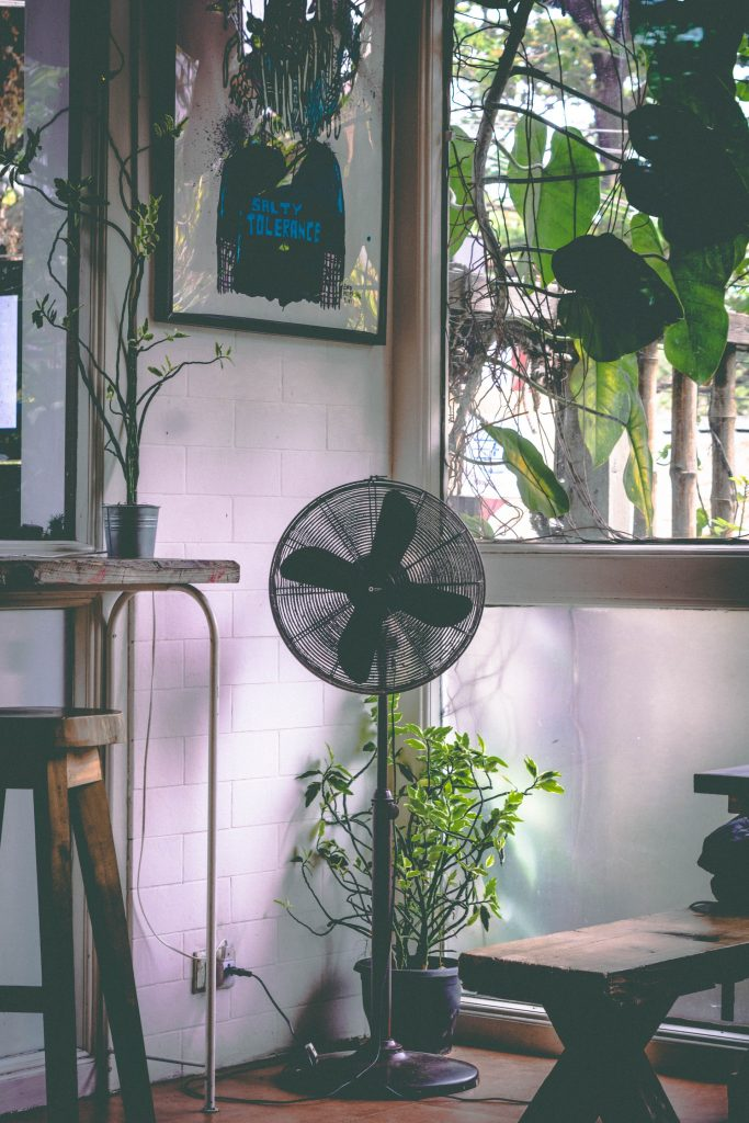 Black fan in the corner of a stylish loft apartment.