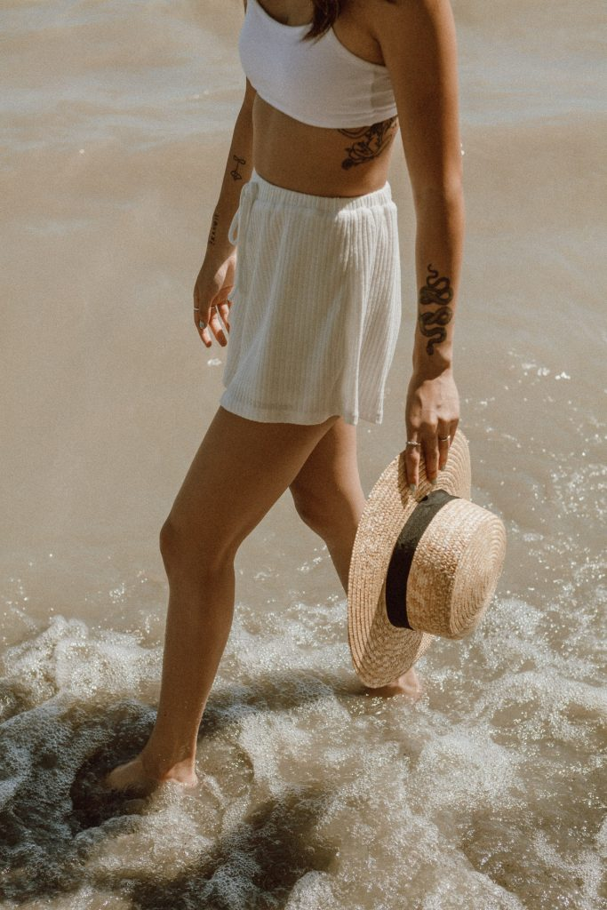 Tattooed woman walking along the beach holding a boater hat.