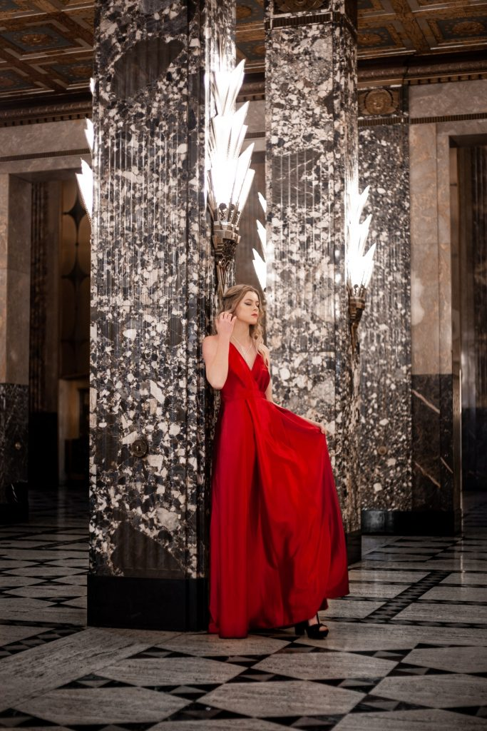 Woman in beautiful red gown leaning against the wall in a fancy hotel lobby.