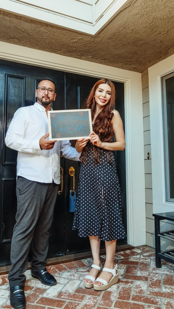 "Couple standing in front of house holding a sign that reads ""Our First Home"""