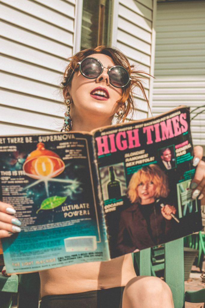 Woman sitting outside reading High Times magazine.