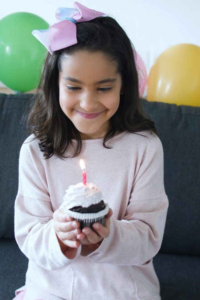 Little girl holding a cupcake with a candle in it.