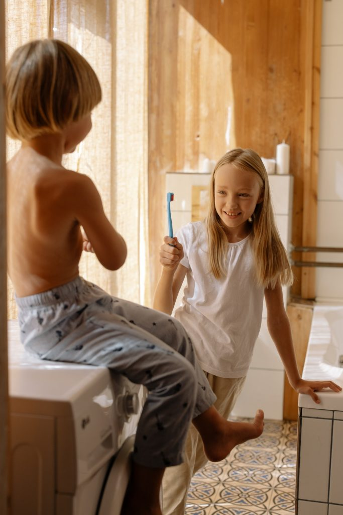 Two kids sitting on a washer and brushing their teeth together.