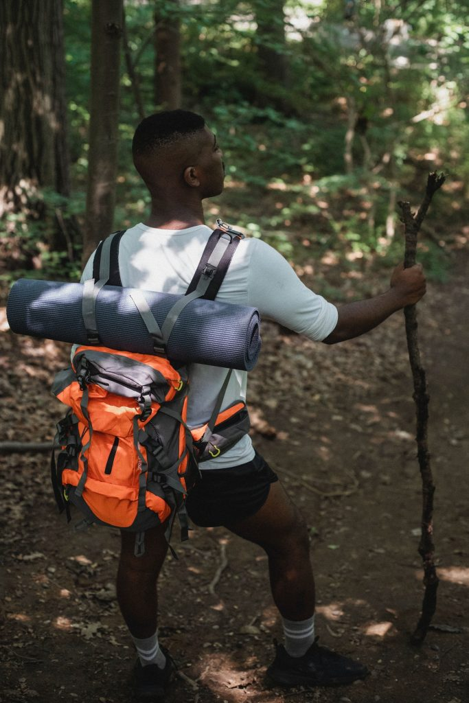 Man in the wilderness hiking with a large backpack on his back.
