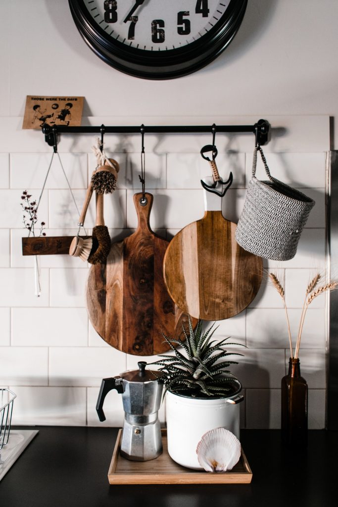A moka pot and a plant on a kitchen counter surrounded by cutting boards.