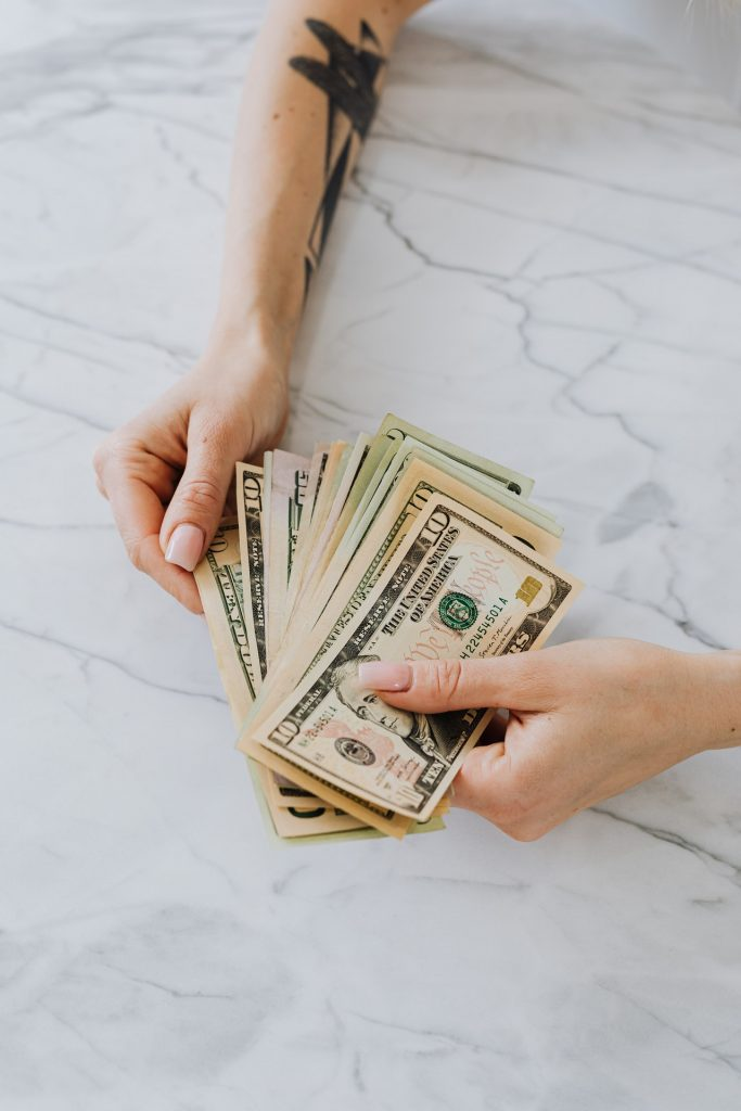 Person holding money over marble table.