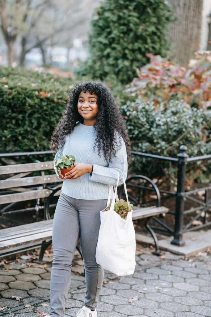 Woman in grey outfit walking in a city park holding a bag of greens in an eco-friendly bag and a plant.