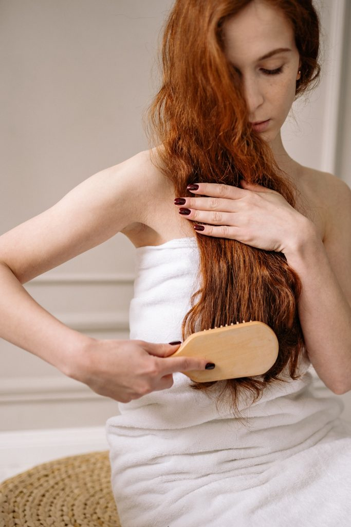 Woman with red hair sitting in bathroom brushing long hair while wearing a white towel.