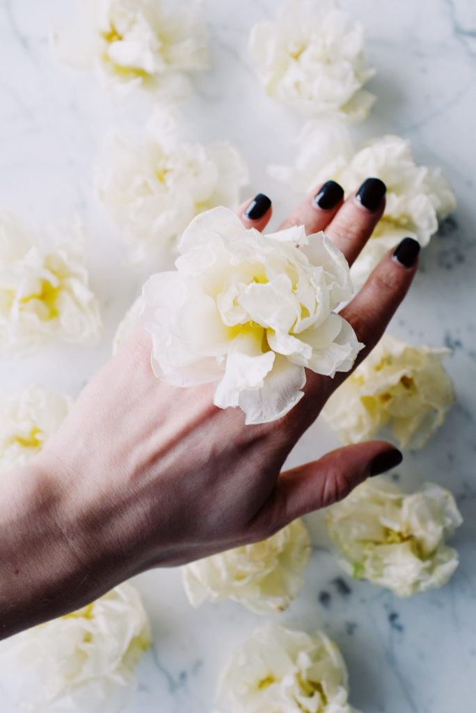 Hand with black nail polish with a white flower on top of it.