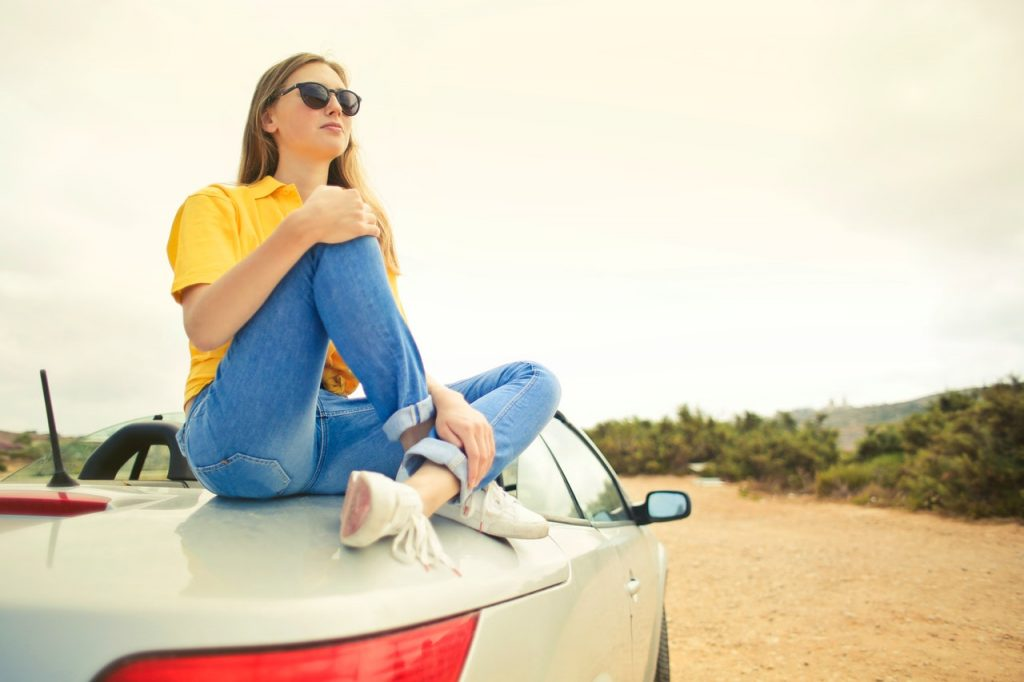 Woman with blonde hair sitting on the trunk of a white convertible on a desert road.