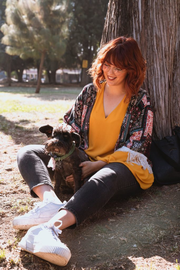 Woman sitting against a tree in a park while holding her small dog and smiling.