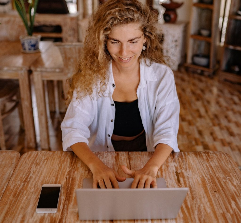Woman with long curly hair smiling and looking at laptop while working on a kitchen table.