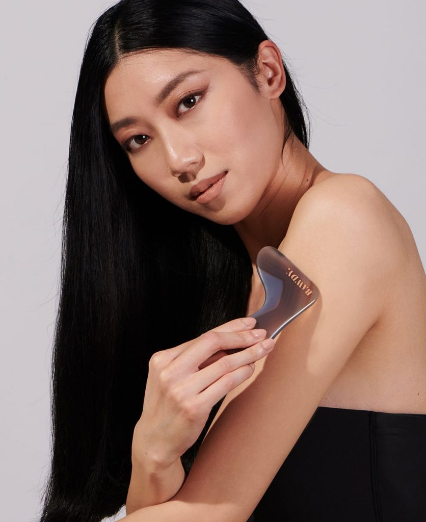 Woman using a gua sha tool for her body.