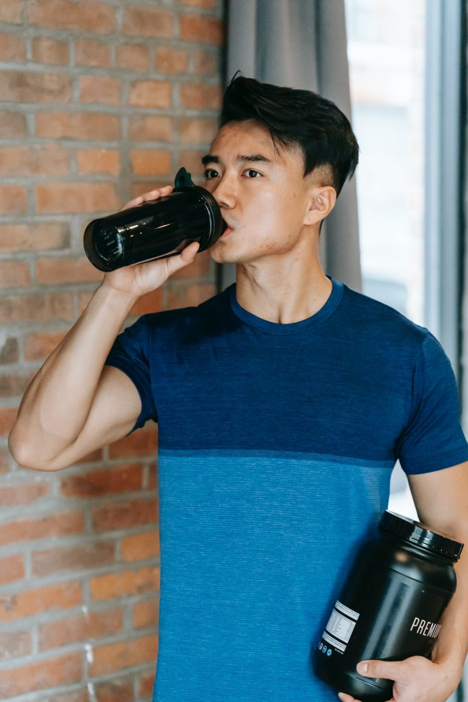 Man in blue shirt drinking a post-workout supplement smoothie in a gym.