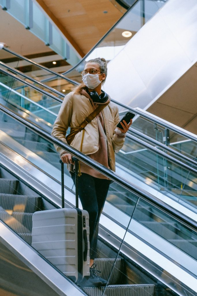 Woman riding down escalator with a large luggage bag at an airport during the covid-19 pandemic.