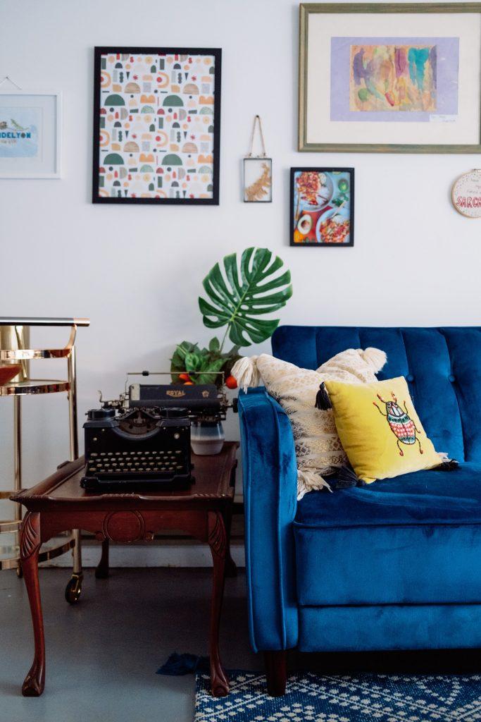 Blue velvet couch with boho chic decor.