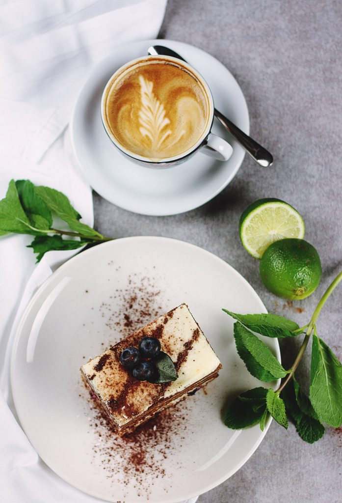 A latte with latte art and tiramisu on a grey table next to lime and mint leaves.