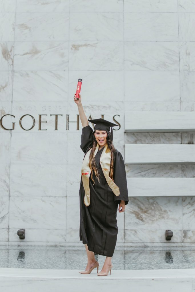 Woman wearing a cap and gown holding up her new degree on graduation day.