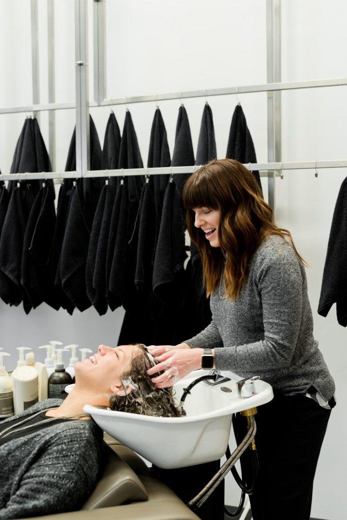 Hairstylist shampooing client at a shampoo bowl in a hair salon.