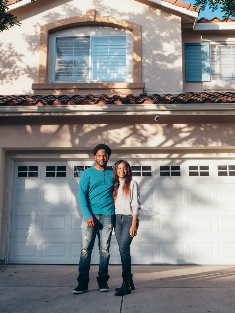 Young couple standing in front of a house they just bought.