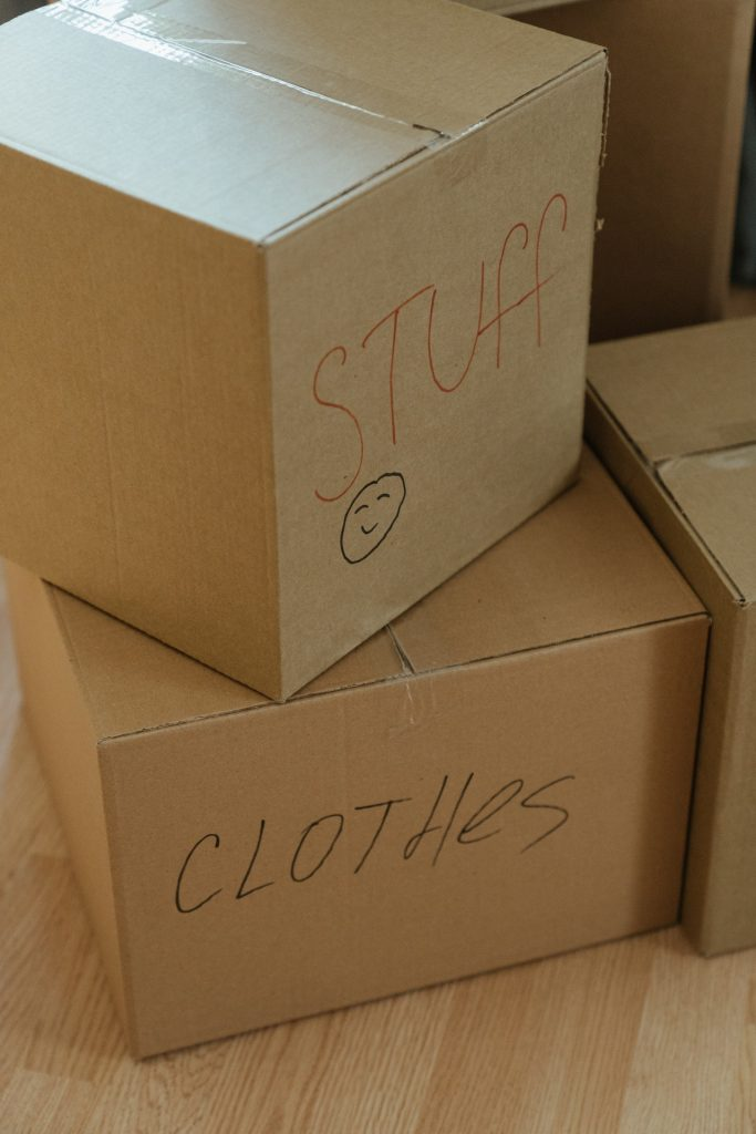 """Stacked moving boxes labeled """"clothes"""" and """"stuff"""" on a wood floor."""