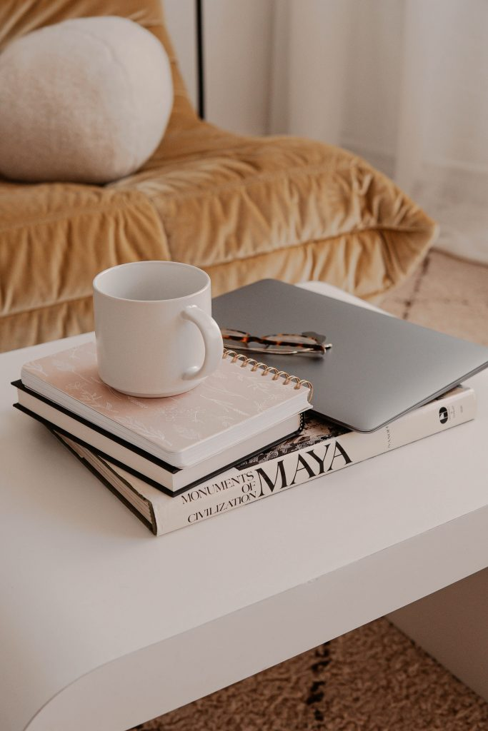 A coffee mug, a laptop, and books on top of a white coffee table.