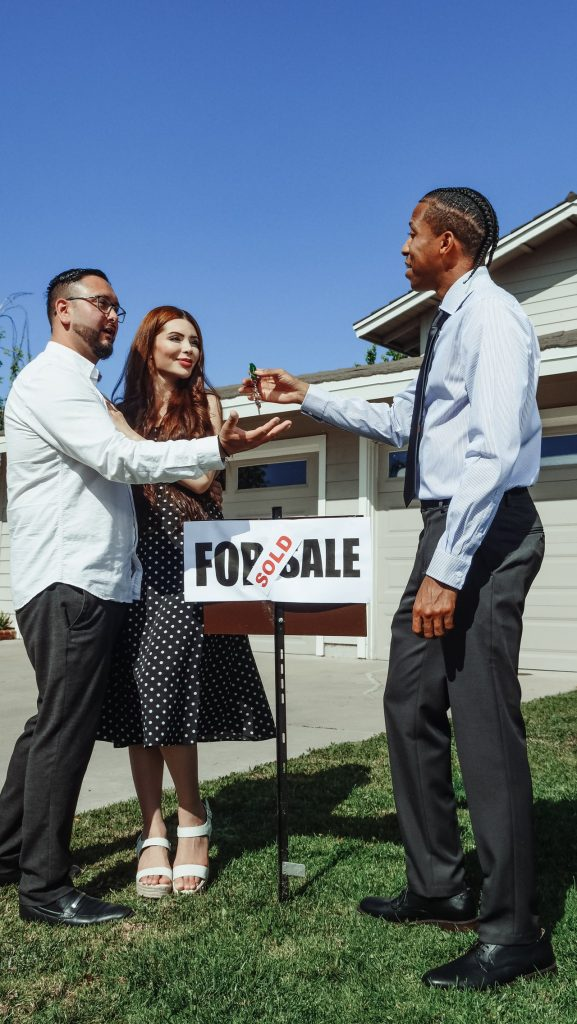 """Real estate agent handing a couple who just bought a home the key in the yard in front of the """"sold"""" sign."""
