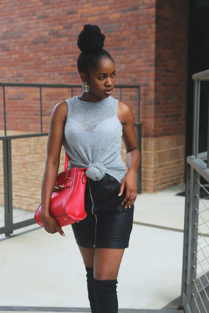 Woman wearing a grey tank, black leather skirt, black boots, and holding a red bag.