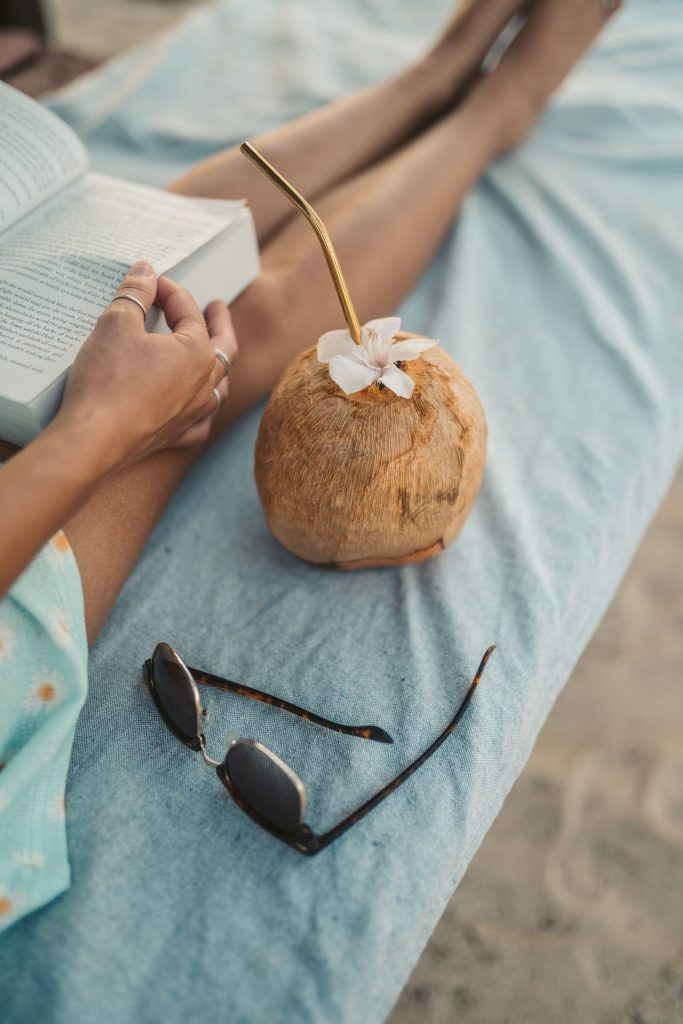 Woman reading on a tropical beach with a coconut.