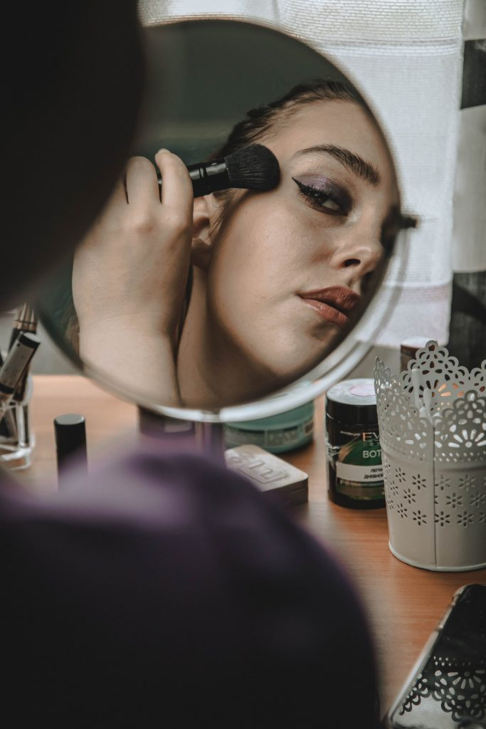 Woman lookin in a mirror applying blush and highlighter.