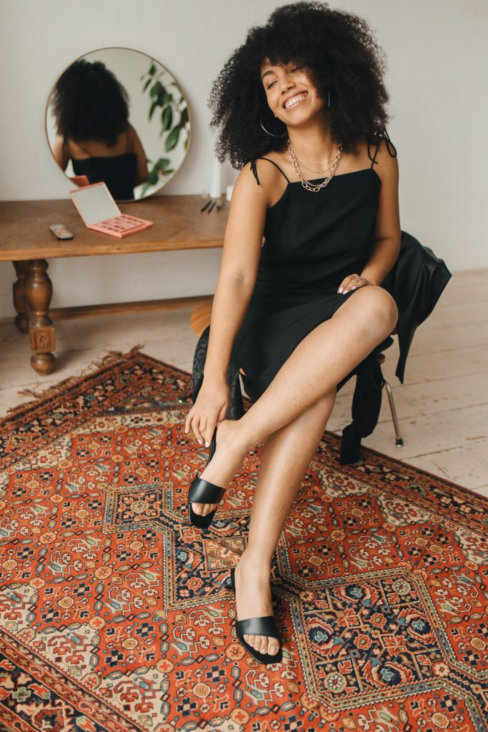Woman with curly hair and wearing a black dress sitting on a chair and putting on black sandals.