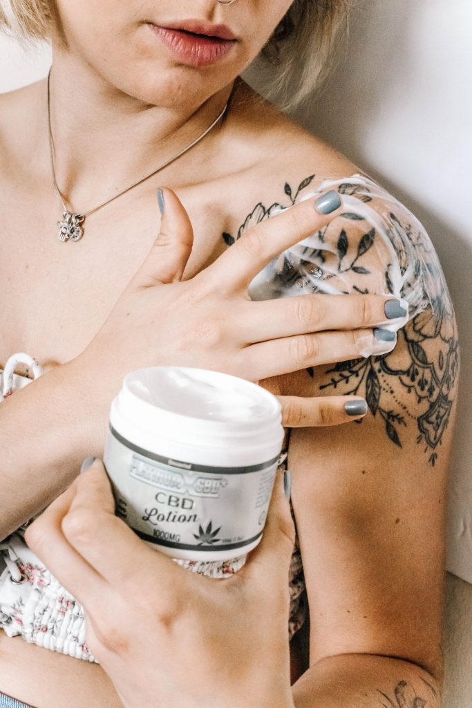 Woman applying CBD lotion to her tattoo on her shoulder.