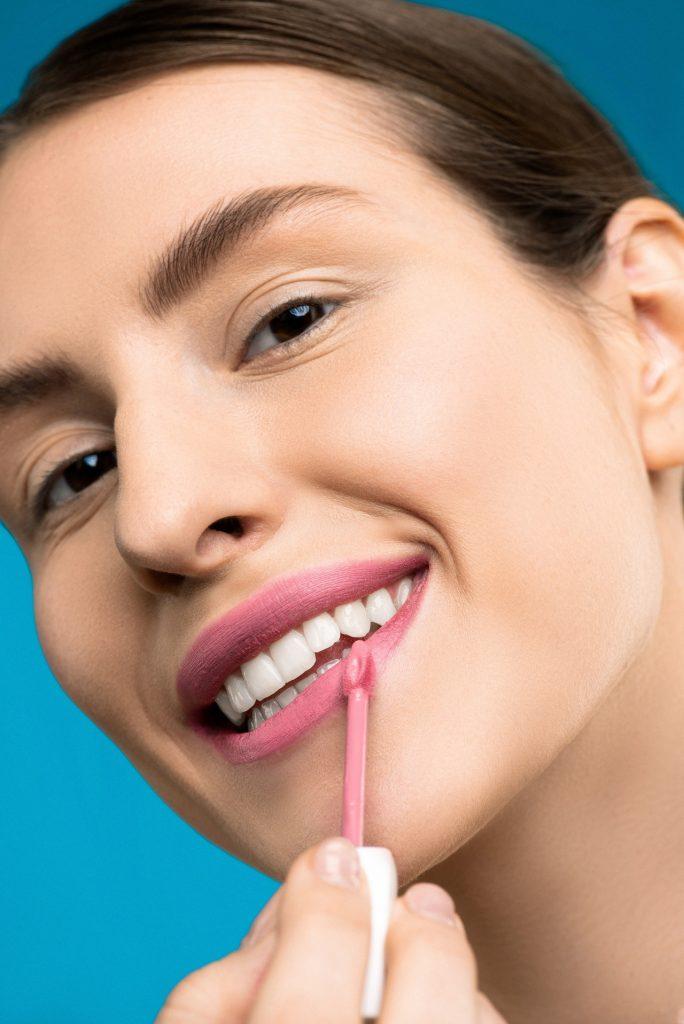 Woman with straight hair applying lip gloss.