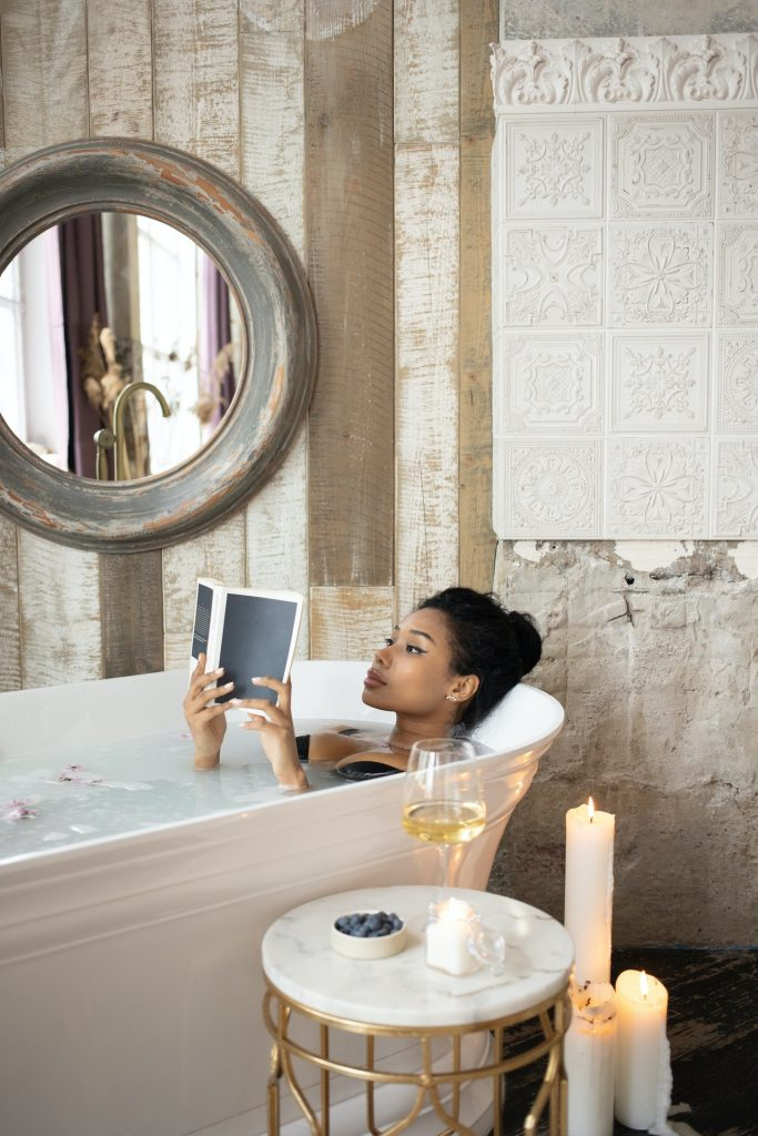Woman taking a bath reading a book and drinking white wine.