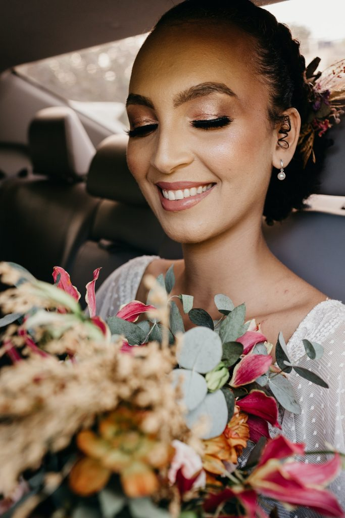 A bride in a limo looking at her flower bouqet.