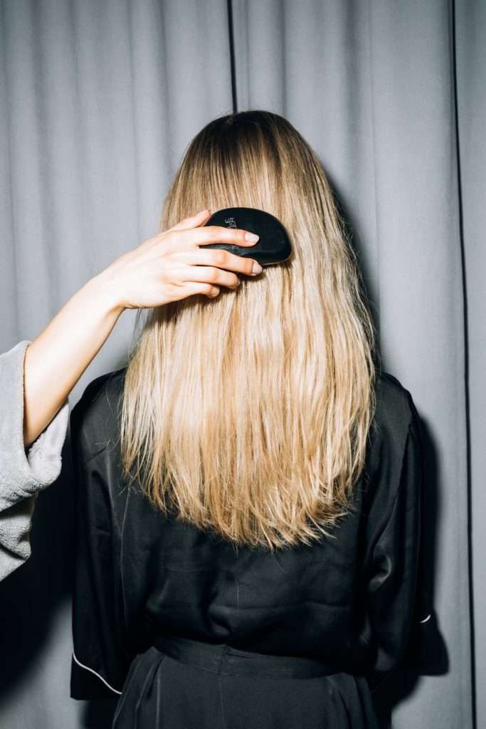 Woman wearing a black bathrobe facing a wall while her long blonde hair is brushed.