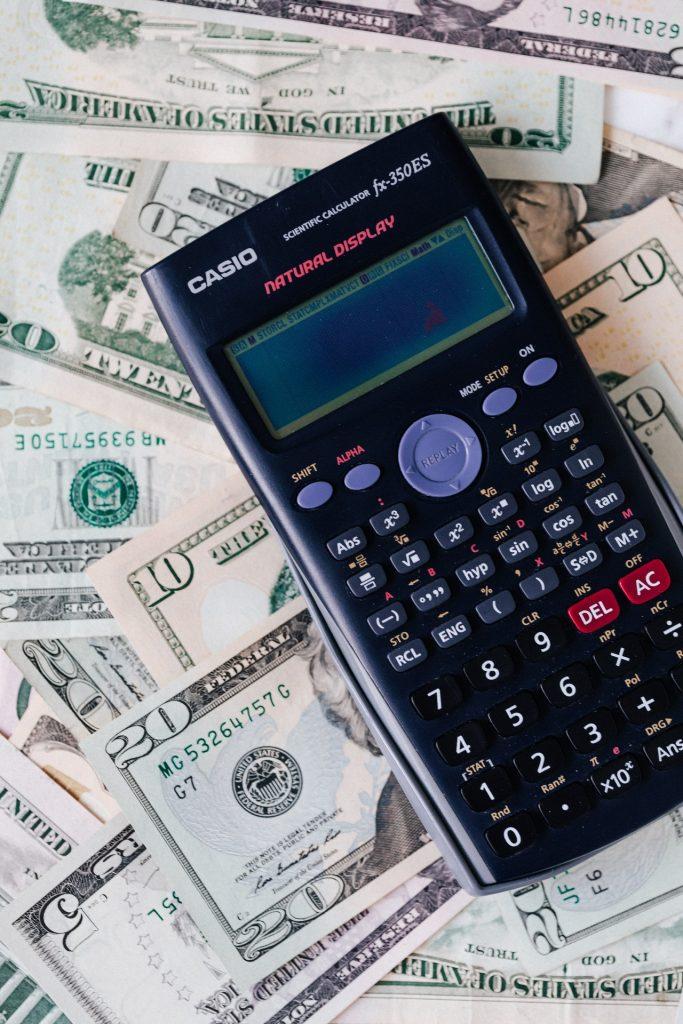 A Casio calculator sitting on top of money.