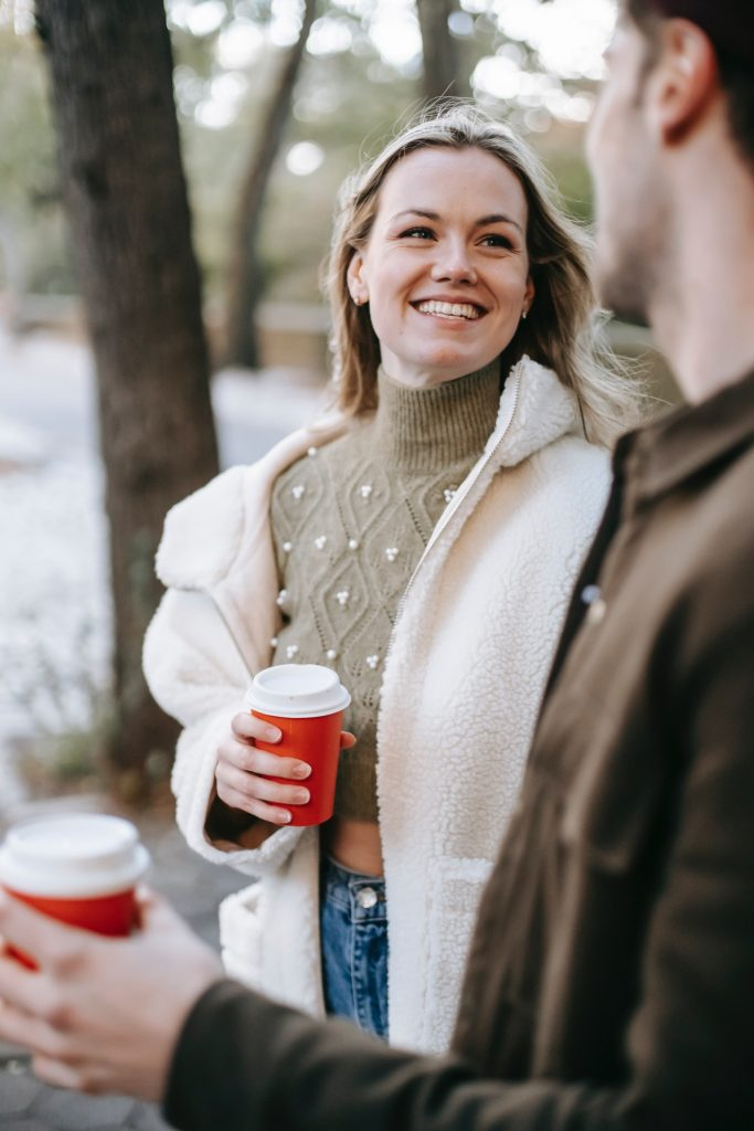 Two people on a first date holding coffee in a red cup and walking through a park.
